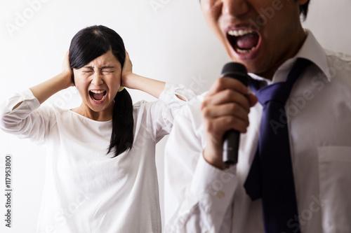 Láminas  カラオケで歌う男と耳を塞ぐ女
