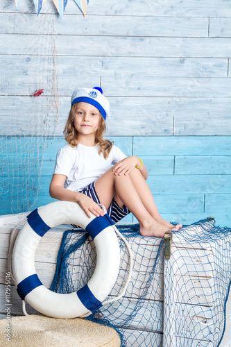Fotografia  Little girl sailor sitting on box