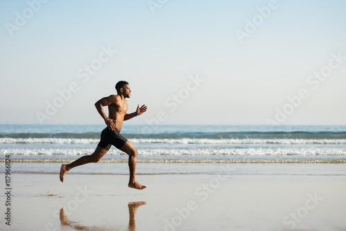Fotografie, Obraz  Black fit man running barefoot by the sea on the beach