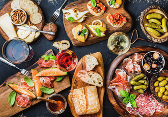 Italian antipasti wine snacks set. Brushettas, cheese variety, Mediterranean olives, pickles, Prosciutto di Parma with melon, salami and wine in glasses over black grunge background, top view