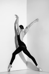 FototapetaBallerina in black outfit posing on pointe shoes, studio background.