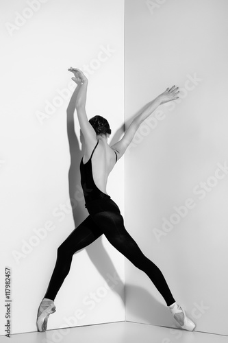 Ballerina in black outfit posing on pointe shoes, studio background. - 117982457