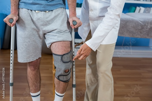 Papel de parede Physiotherapist helping patient to walk with crutches