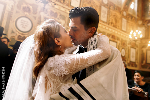 Fotografía Blessed kiss of Jewish wedding couple standing in the synagogue