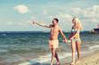 happy couple in swimwear walking on summer beach