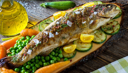 FototapetaGrilled trout fillets with vegetables on wooden background