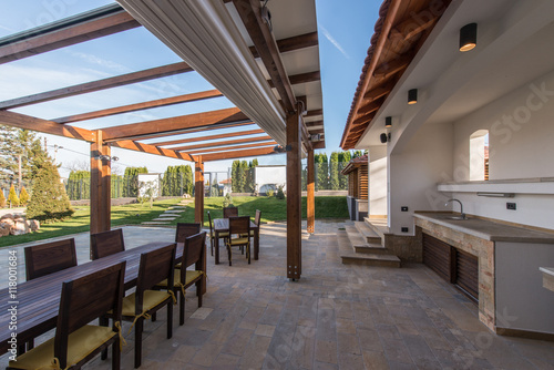 Beautiful terrace lounge with pergola and wooden table with chairs Fototapeta