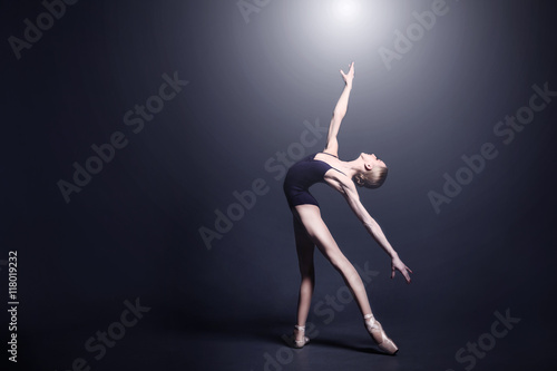 Fotografie, Tablou  Young ballerina in a black suit is dancing in a dark studio