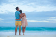 couple in bright clothes walking at the tropical beach in the evening