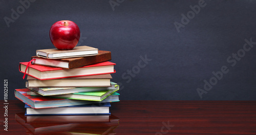 Pile of books and red apple on the desk over the blackboard