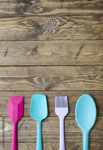 Colorful kitchen utensils arranged on a distressed wooden ...