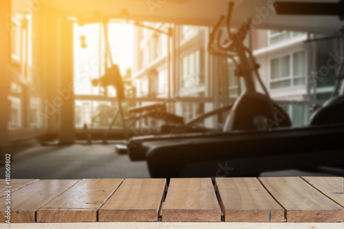 Empty top wood table and blur fitness gym background