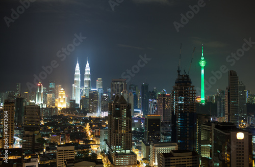 Photo Stands Kuala Lumpur Panorama of Kuala Lumpur at night. Illuminated buildings and skyscrapers in the capital of Malaysia. Menara KL Tower and Petronas Towers dominating over the city architecture