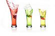 Splash of strawberry thrown into a glass. Three different colored drinks with strawberries, yellow, green and red.