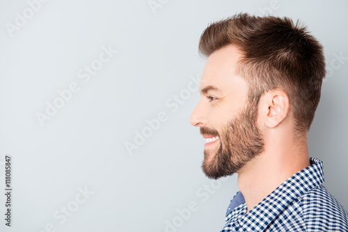 Valokuva  Side view of young happy smiling bearded man