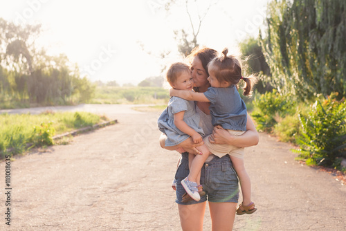 Photographie  Mother holding two girls on hands