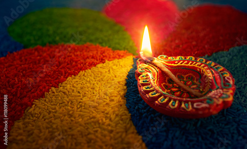 Diwali oil lamp - Diya lamp lit on colorful rangoli