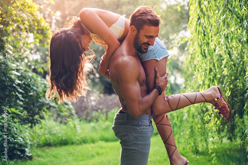 Fototapety, obrazy: Man holding his girl up and laughing