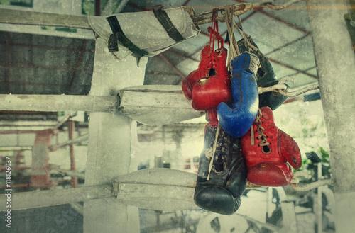 Fototapeta Para starych bokserskich rękawic Muay Thai wisi na ringu w obozie slumsów. Dodany efekt dodania do stworzenia atmosfery