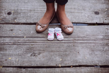 Mom And Her Future Child. Close-up Of Legs Of Young Pregnant Model Stay On Wood Pier Near White Tiny Booties For Her Baby. Maternity Concept. Outdoor