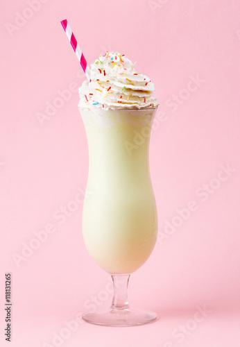Foto op Plexiglas Milkshake Glass of vanilla milkshake with whipped cream on pink background