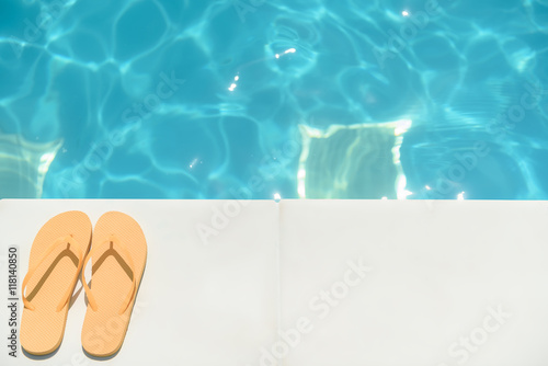 Photo Flip flop shoes near blue water