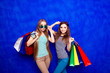 Leinwandbild Motiv Pretty stylish girls in glasses holding packs with new clothes