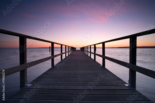 Long Wooden Pier into a Lake at Sunset, perfect symmetry Wallpaper Mural