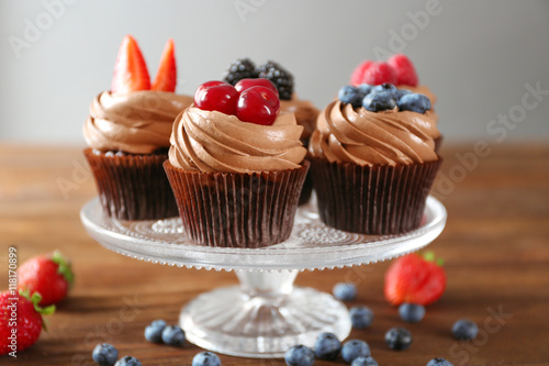 Photo  Tasty chocolate cupcakes with fresh berries on stand
