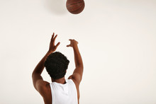 Back Shot Of A Muscular Fit Black Player In White Sleeveless Shirt Throwing A Brown Leather Basketball Away From Camera Isolated On White