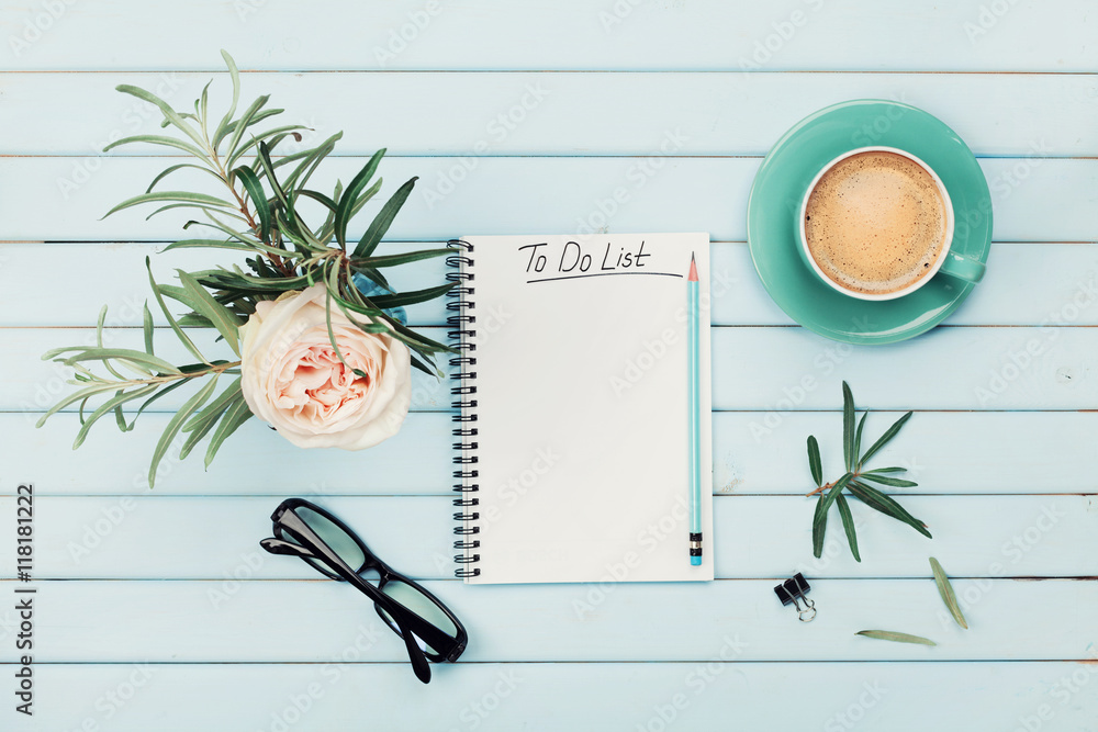 Fototapeta Morning coffee cup, notebook with to do list, pencil, eyeglasses and vintage rose flower in vase on blue rustic table from above. Planning and design concept. Cozy breakfast. Flat lay styling.