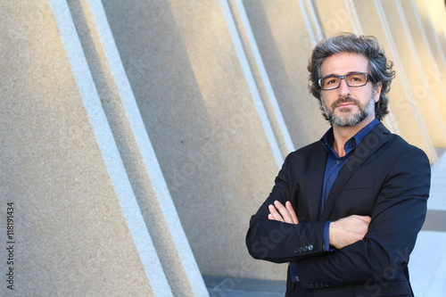 Cuadros en Lienzo Mature elegant professional with his arms proudly folded standing outside the of