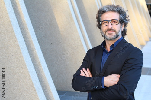 Mature urban business man with specs crossing his arms