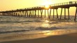 Long boardwalk pier stretching above tranquil afternoon waves in golden sunset, shot in Los Angeles, California