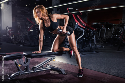 Fotografía  Girl pumping up muscles with dumbbells