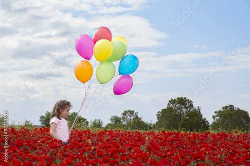 Photo  Little girl on  field with wild flowers and many colorful balloons