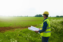 Surveyor With Blueprint Looking Out Over Farm Field