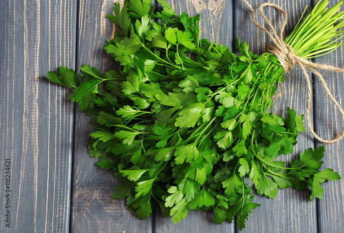 Fresh bunch of parsley closeup on wooden table. Top view