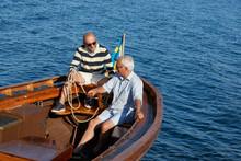 Friends Sitting In Boat On Ocean