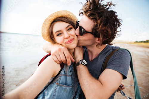 Fotografía Couple kissing and taking selfie outdoors