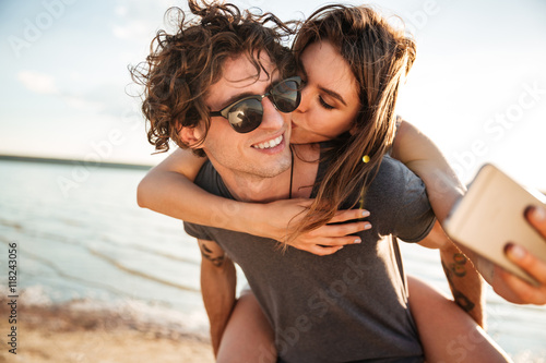 Fototapeta Young happy couple kissing and making selfie at the beach obraz