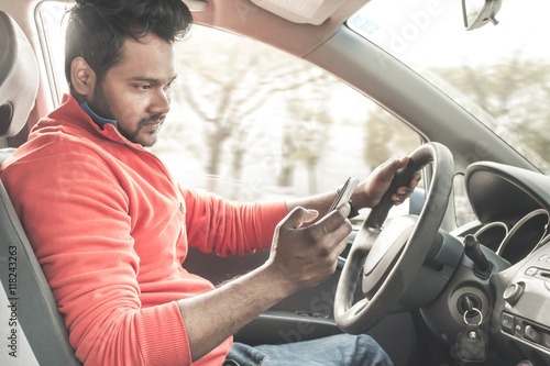 Fotografia, Obraz  reckless driving - indian driver distracted by smartphone