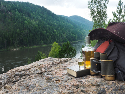 Poster Camping Bottle with alcohol and tourist equipment on the background of forest