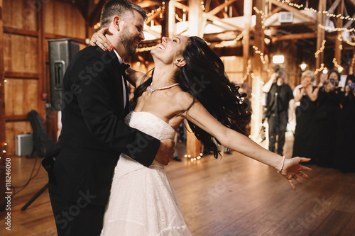 Fotografia Bride shakes her dark hair while dancing with a groom in wooden