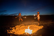 Two young girls holding sparklers on beach beside campfire, holding sparklers