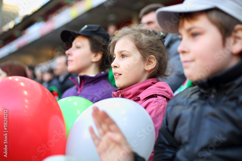 Papiers peints Attraction parc Serious girl with mother and brother among fans at stadium