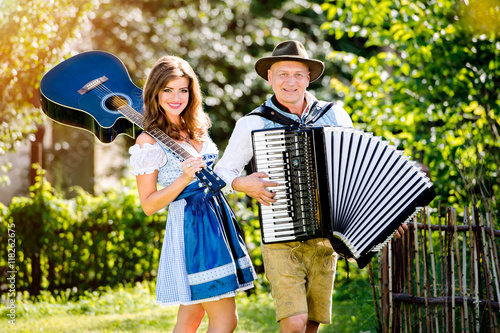 Couple in traditional bavarian clothes with guitar and accordion Poster Mural XXL