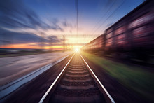 Railway Station With Cargo Wagons And Train Light In Motion At Sunset. Railroad With Motion Blur Effect. Railway Platform. Heavy Industry. Conceptual Background