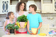Happy mother with son and daughter look at each other with houseplants in the kitchen