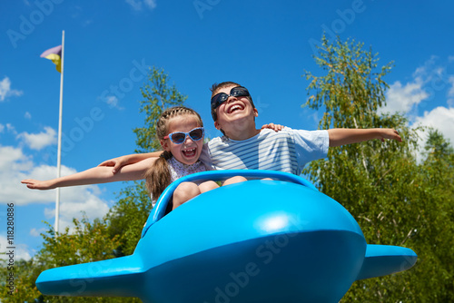 Foto  child girl and boy fly on blue plane attraction in city park, happy childhood, s